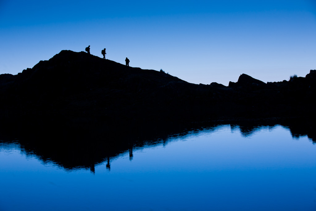 Trekkers reflected in a lagoon