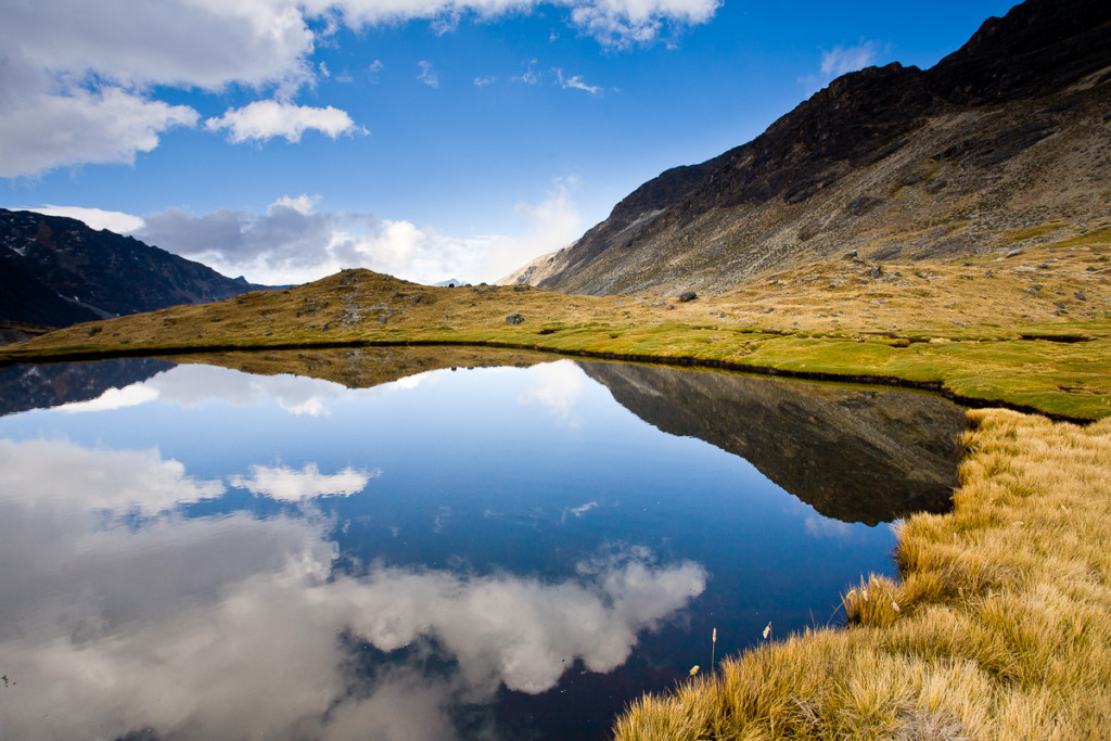 A high-altitude bog lies at 15,750'/4,800m and is across the way from Mt. Sunchuli (17,200'/5,300m) and reflects the peaks of the Apolobamba Range in Bolivia during winter.