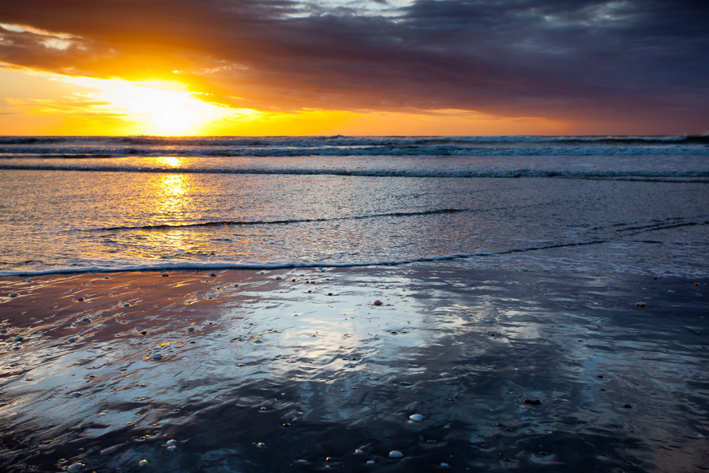 A storm is reflected on the wet sand of Otaki Beach on the west coast of New Zealand's North Island as a storm moves in at sunset.