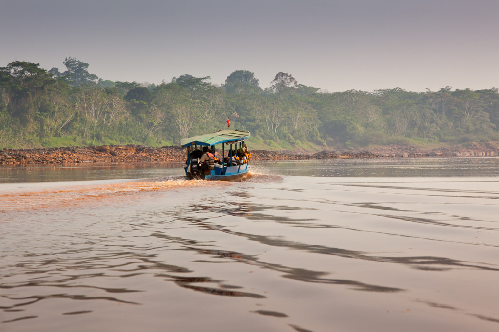 Tourists travel to lodges deep in the jungle via motorized boats