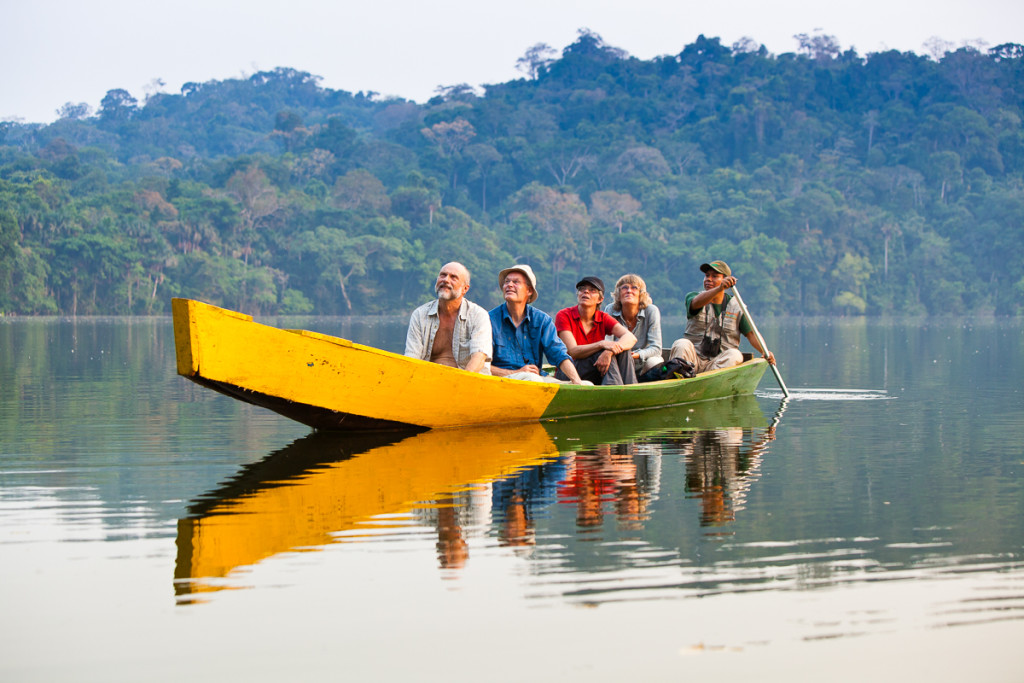Tourists and guides travel via canoe along the edges of Chalalan